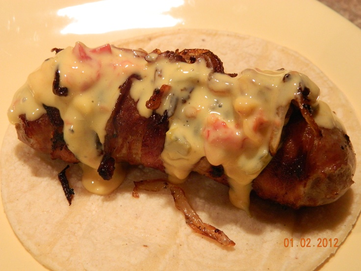 bacon wrapped beer bratwurst topped with grilled onions and queso
