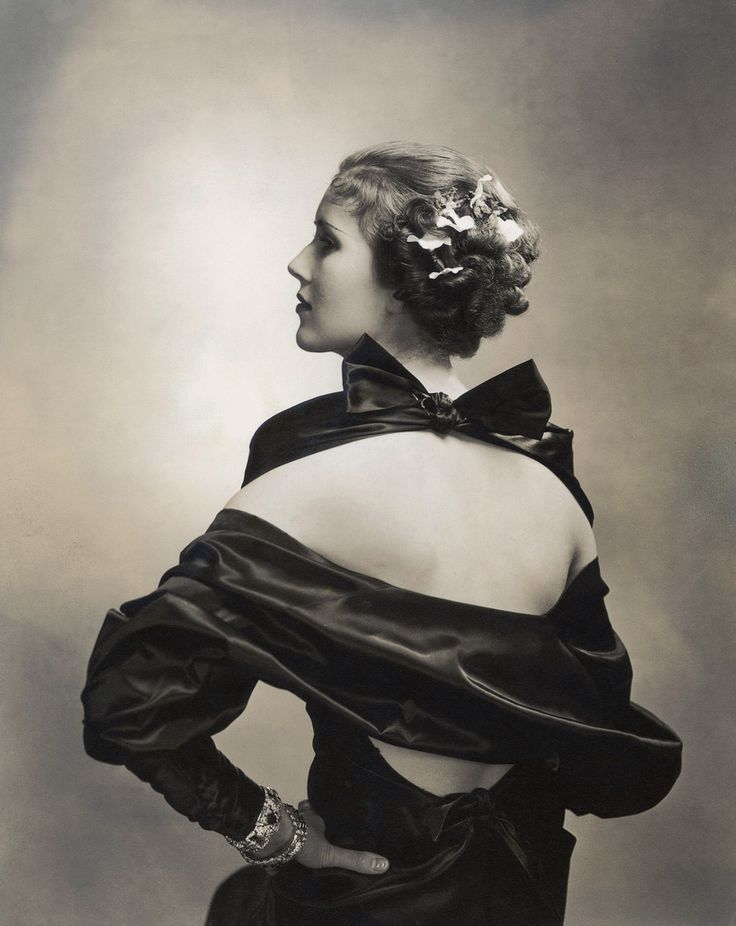 The most sought after portraitist of the 1920s and 1930s. Edward's use of dramatic lighting and spare backdrops revolutionized celebrity photography. Here, Edward Steichen's elegant black and white composition captures actress Mary Heberden from the back, wearing an off-the-shoulder black satin dress and orchids in her hair.   The portrait appeared in Vogue March 1935