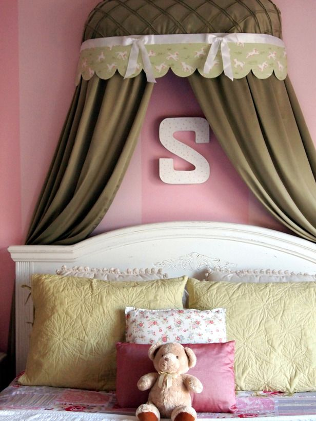 A forest-green bed crown is the perfect addition to this pastel-pink girls' bedroom.
