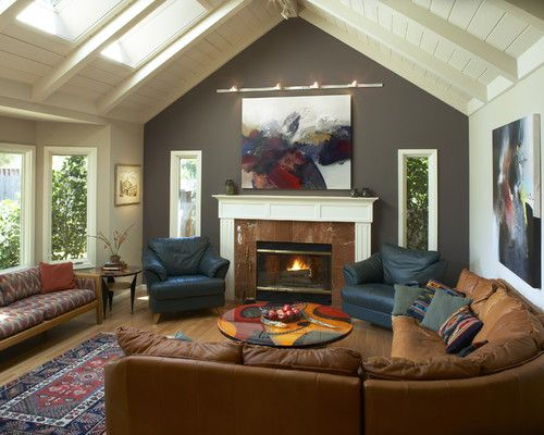 Dark brown couch sofa with Sherwin WIlliams Black Fox Wall and Greek Villa trim also abstract painting above fireplace nad light white ceiling