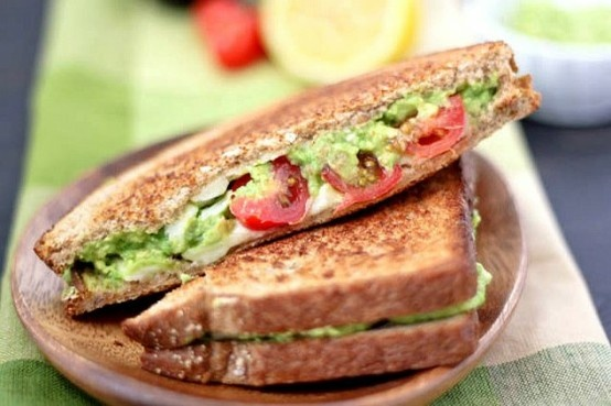 Grilled cheese sandwich with tomatoes and avocado.
