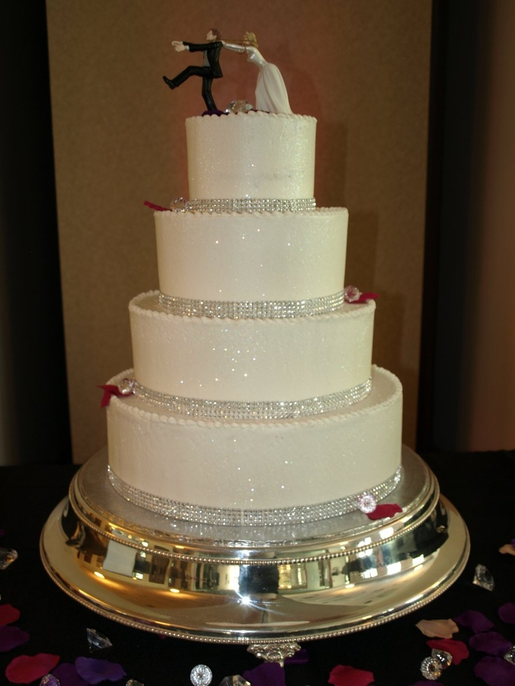 Reluctant Groom Wedding Cake, rhinestone bands, glitter, glitz, diamonds,red and purple petals, clean lines.  Winter Park Community Center  www.cakedesigners.net