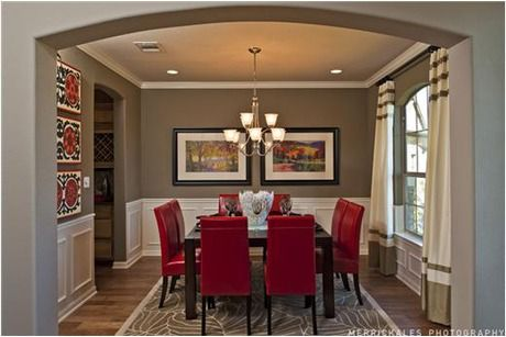 Red leather chairs pop against gleaming white wainscoting and dark paint. The Hampton Model by Taylor Morrison. The Ladera new home community in Bee Cave, Texas, near Austin.