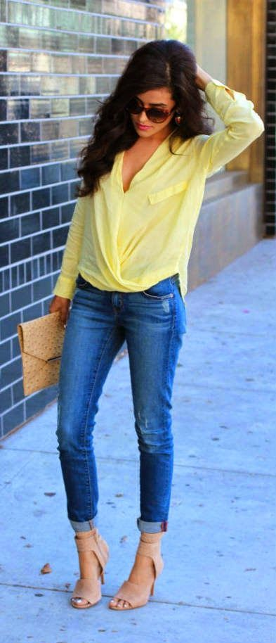 Beautiful denim blue stylish jeans with top bright yellow stylish blouse and light brown stylish plain leather clutch and off pink high heels ladies sandals the best summer street style outfits