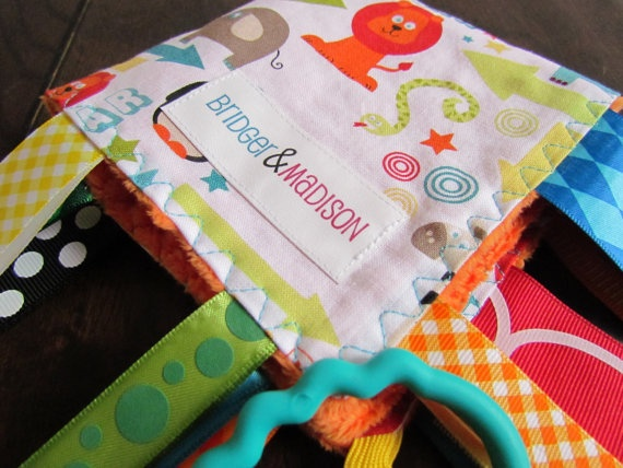Educational tagEducational tagblanketswith sewn shut ribbons for added safety. A perfectEducational tagEducational tagblanketswith sewn shut ribbons for added safety. A perfectbabyshower gift and also a therapy toy for special needs. Milwaukee Mom business.