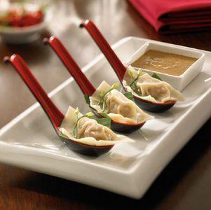 Pork dumplings with walnut sauce on cute spoons.