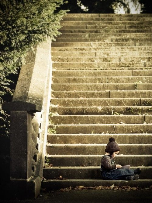 young child reading on steps