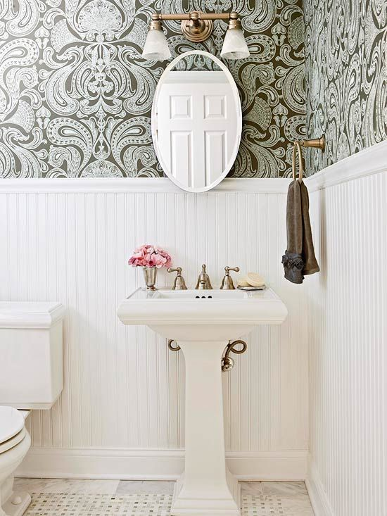 BHG    Gorgeous powder room with light gray & chocolate brown damask wallpaper, chair rail & beadboard, glossy white pedestal sink, marble tiles with marble basket weave inset tiles, oval pivot mirror and brass towel holder & frosted clear glass double sconce in brass.
