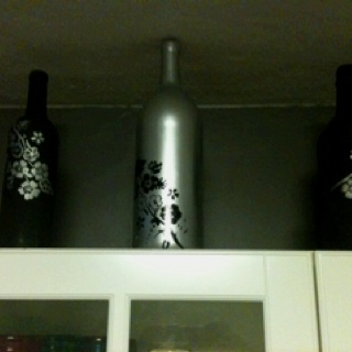 Reuse empty wine and liquor bottles for pretty decor - use spray paint & stencils ;)