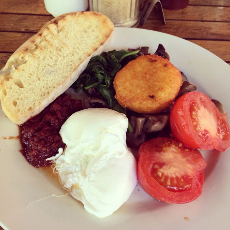 Vegetarian breakfast with poached eggs, toast, spinach, tomatoes ...