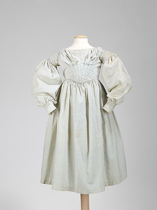 Girl's dress, American, 1837-40. It is charming to see period dresses produced in miniature sizes for children, and the dress shown is a very high-style garment. It is a perfect example showing the collapse of the gigot sleeve in 1837 and the beginning of the V-shaped form of bodice in the 1840s. Additionally, the puffing over the bust adds another adult dimension.