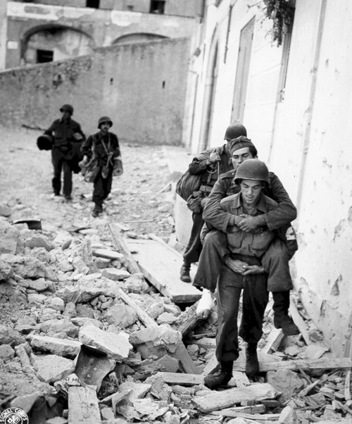 An American medic carries a wounded German POW.