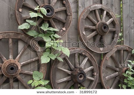 Old rusty woden wagon wheels, used as a garden decorating  shutterstock.com