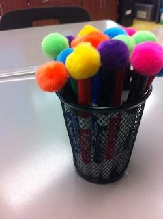 Hot glue pom poms onto dry erase marker caps to make quick and easy erasers!