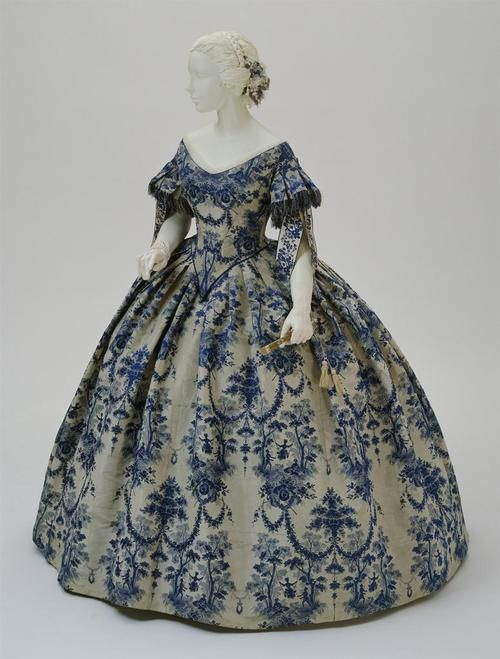 """French evening dress with swing motif, c.1850-55 (via).    """"This evening dress of about 1850, with its bodice deeply pointed at the waist, pleated sleeves trimmed with fringe and figured ribbons, and full, bell-shaped skirt, exemplifies the opulence of Second Empire France (1852-70). The fabric itself, a Jacquard-woven silk produced in Lyons, reveals the derivative nature of mid-nineteenth-century textile design, which often used elements"""
