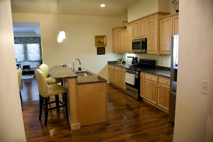 Kitchen maple cabinets with natural finish pendent lights under