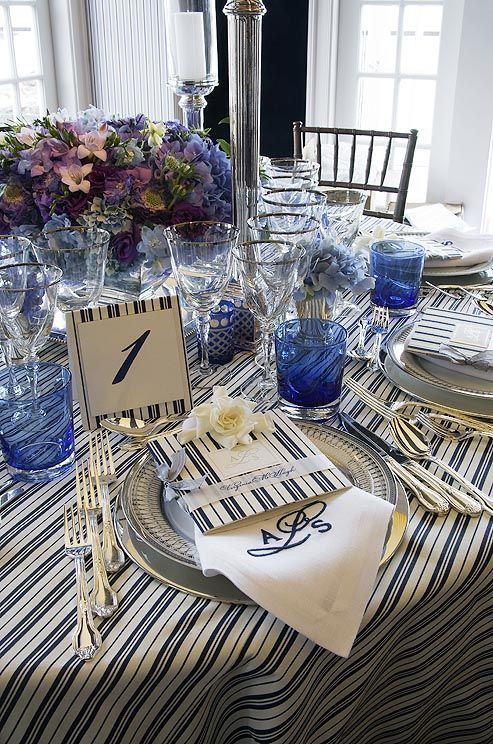 A navy blue and white striped table is set with a matching table number, menus and monogrammed napkins. See more #wedding decor inspiration: http://ccwed.me/JVfL3O