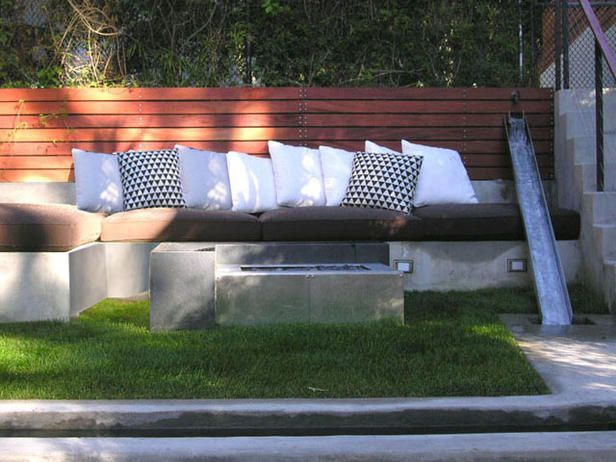 A water feature made from a stainless steel runnel and a modern fire pit create a sleek look.