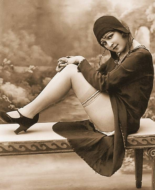 STUDIO PORTRAIT - WOMAN SITTING ON BENCH IN FLAPPER OUTFIT SHOWING HER LEGS