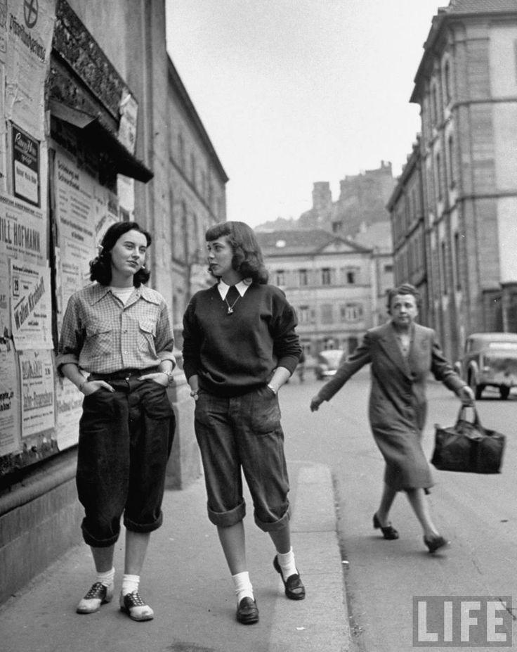 """In the late 1940s American girls (and boys) spice up Heidelberg, Germany in an unruly mix of saddle shoes and lederhosen. The locals gawk and gasp as young girls parade down the streets decked in men's flannels, trousers and loafers. (I'm guessing red lipstick is involved somewhere.) Shocking the Germans as they reappropriate various Heidelburg traditions into trendy accessories—old university caps, miniature Heidelberg sabersons, and military patches. American invasion!"""