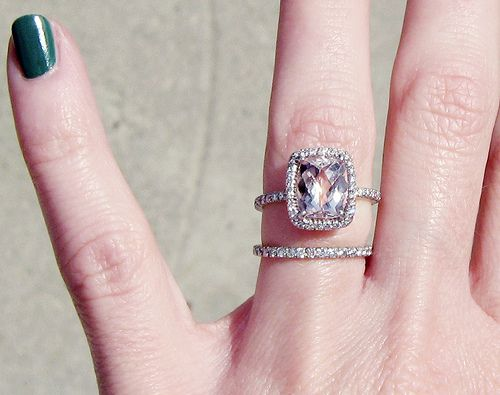 engagement ring is a 3 karat rectangle cushion cut light pink/peach Morganite {aka: pink beryl, rose beryl, pink emerald, & cesian beryl}  A morganite doesn't sparkle as much as a diamond so the extra facets add sparkle. Morganite can really get more bang for the buck, It's far less expensive than a pink diamond but has the same effect.