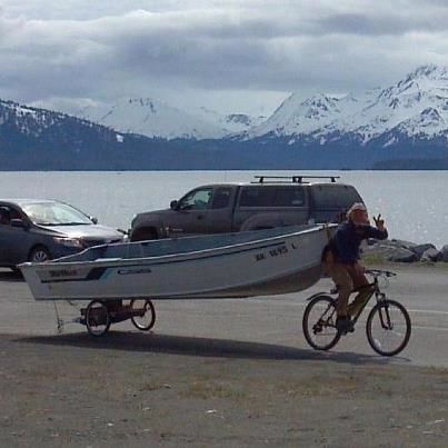 Biking and boating! A cyclist uses ingenuity to move a boat in the Spit area of Homer.
