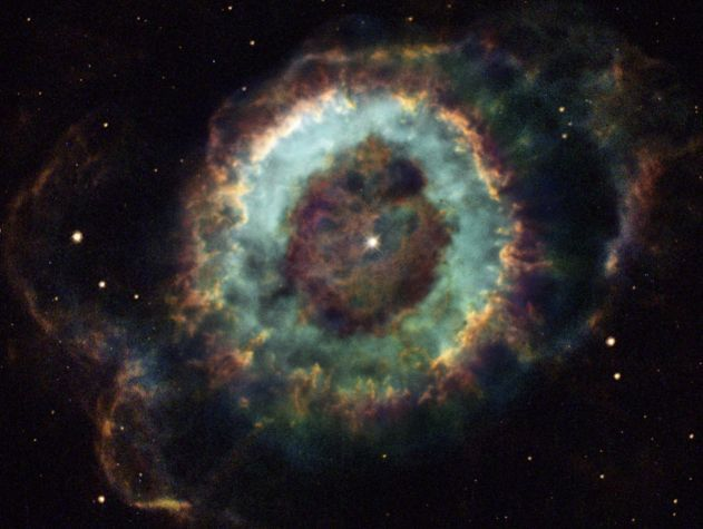 """The Little Ghost Nebula is a planetary nebula. Nothing to do with planets, but they looked like planets in 18th century telescopes.  Planetary nebulae form when a star like the Sun runs out of hydrogen and swells into a red giant, throwing off the outer layers of atmosphere.  This often happens fairly symmetrically.  (Image: Hubble Heritage Team)  ©Mona Evans, """"Nebulae"""" http://www.bellaonline.com/articles/art43407.asp"""