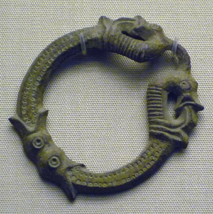 Copper alloy pseudo-penannular brooch; 10th-11th c; Ala, Gotland, Sweden  flat hexagonal section; cast opposed animal heads at centre of hoop; ring-and-dot, ribbed, punched and incised linear decoration; terminals cast as two profiled backward-biting animal heads.