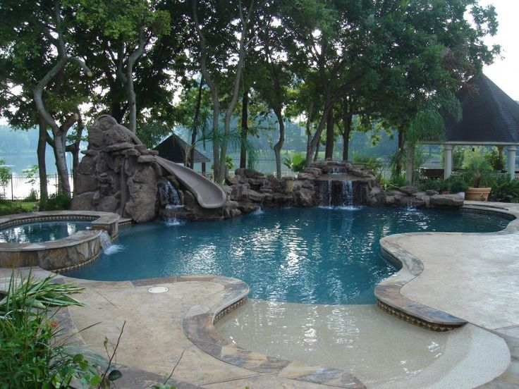 Inground swimming pool with waterfalls and slide and beach access ...