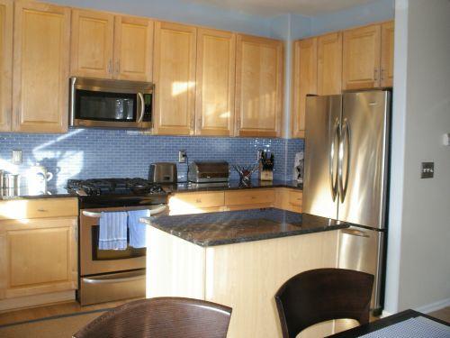 appliances, blue black granite counters, light natural cabinets