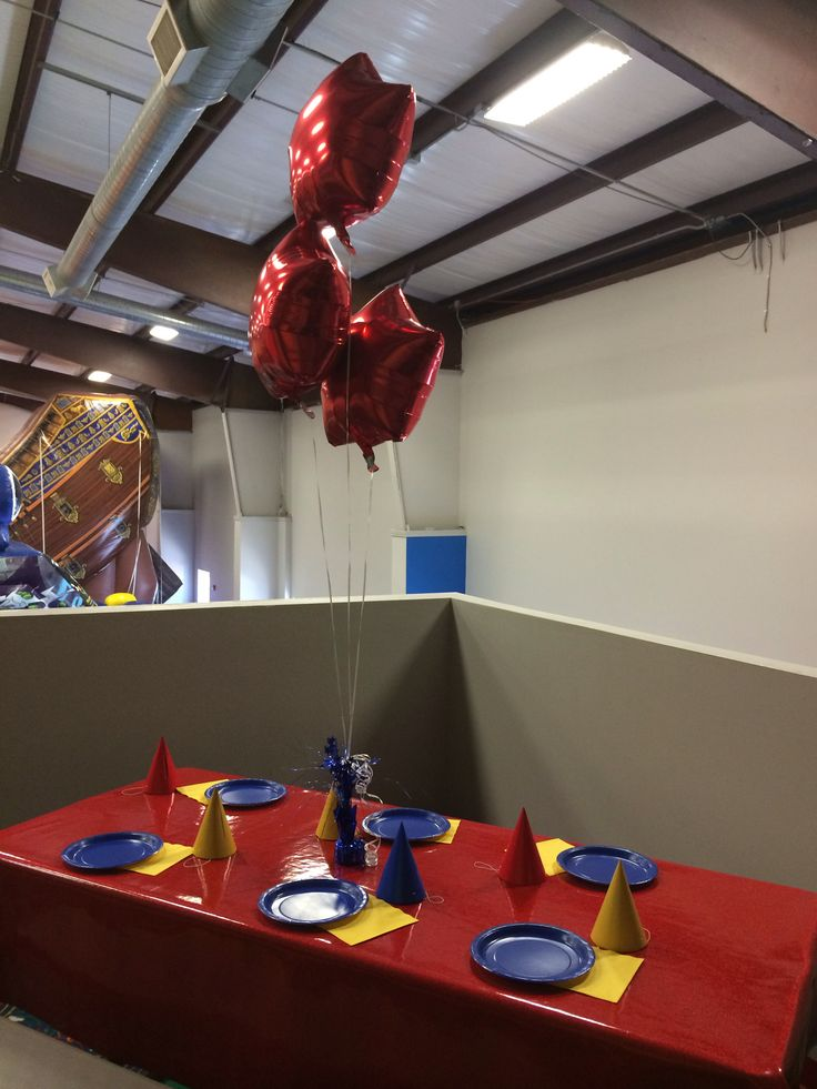 ... napkins, red tablecloth, and party hats in red, yellow, and blue