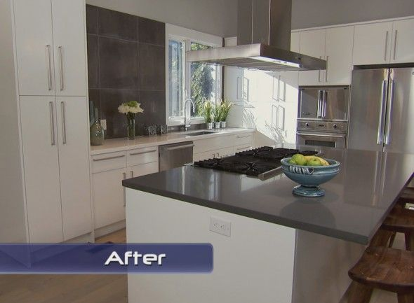 cabinets and grey quartz countertop with large grey tiles on wall