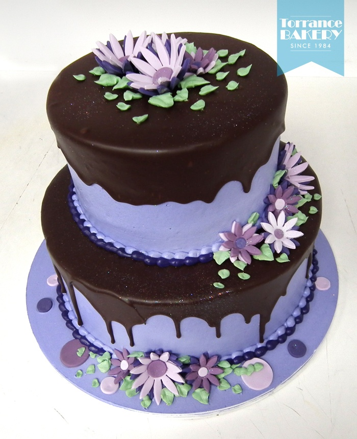 Tiered cake iced in purple buttercream with a rich chocolate fudge ...