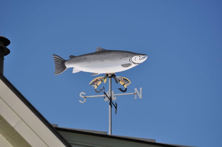 This weather vane was crafted by Warren Gilker (1922-1998), and commemorates the second-largest Atlantic salmon ever legally caught in Canada, a 55-pounder brought in by Victor Albert Stanley. Gilker, a third-generation blacksmith, began making weather vanes in 1980. Formerly a camp manager and head warden on Canada's Grand Cascapedia river, Gilker crafted his first weather vane in 1980 at the request of Jane Engelhard, who wanted to commemorate her late husband's largest salmon catch.