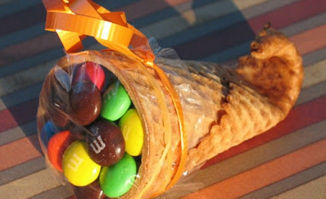 Mini cornucopias made from sugar waffle cones. Fill with little tasty treats. How cute would these look filled with candy corn and pumpkins? Cute for each place setting at Thanksgiving and will keep the kids busy!