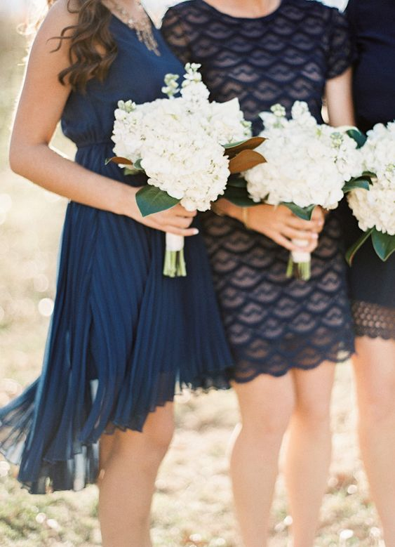 Mix-and-match navy bridesmaid gowns in differing textures come together for a look that's classic and chic.