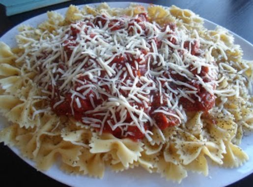 Bow tie pasta with tomato sauce and Parmesan cheese on top