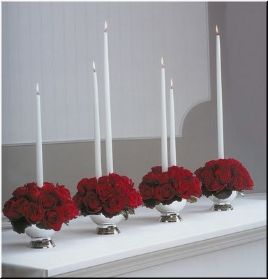 brings out the light and silver with the flowers  Red roses and white tapered candle flower centrepiece