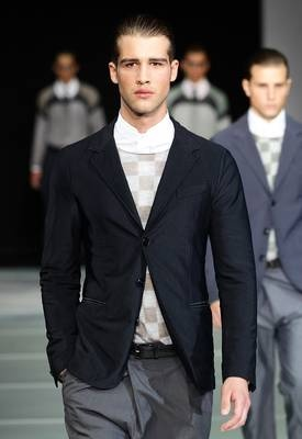 Giorgio Armani/This model walks the runway in a trim 3-button unconstructed blazer with a checkerboard print sweater underneath and baggy grey trousers. This is the kind of outfit you could wear to a variety of summer occasions, from formal to casual.