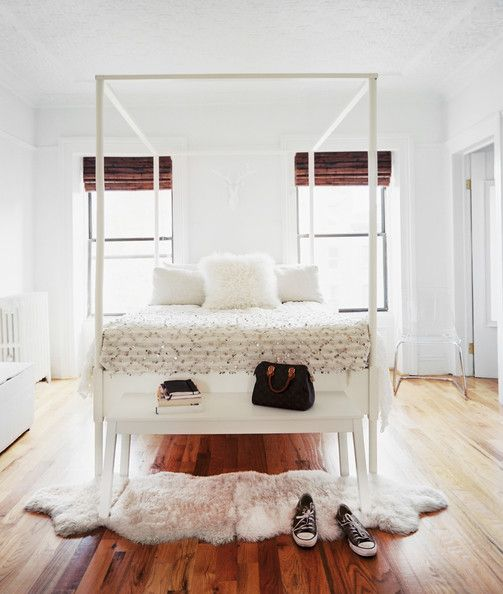 White bench and a pair of sheepskin rugs at the foot of a white canopy bed.  Minimalist. The Moroccan bedspread makes it more global chic.