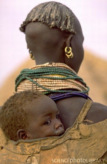 Africa | Bumi woman carrying a child on her back.  Murle region, Ethiopia Woman from the Bumi tribe of Ethiopia, carrying a child on her back.  | © Art Wolfe.
