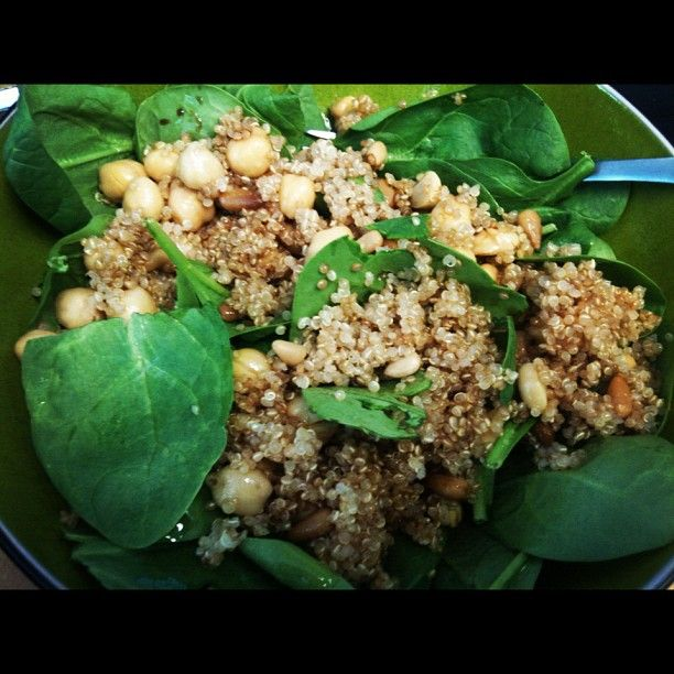 Spinach salad with toasted quinoa, pine nuts, and garbanzo beans.