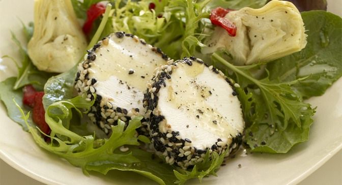 salad of baby greens topped with baked black sesame seed-coated goat ...