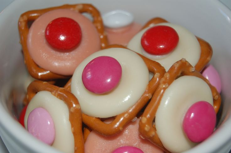 Valentine's Day treats-pretzel snaps, white or pink chocolate melting discs, M&Ms-Preheat; oven to 350 degrees.  Place pretzels right side up on a baking sheet. Place a chocolate disk on each and carefully place in the oven for 2 minutes, just long enough for the chocolate to begin to melt. Pull the tray out of the oven and quickly press one M&M; onto the center of each chocolate disk. Put the tray in fridge to set.