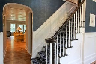 Blue grasscloth + white wainscoting + patterned rug on stairs