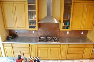 copper backsplash with zinc countertop yellow cabinets