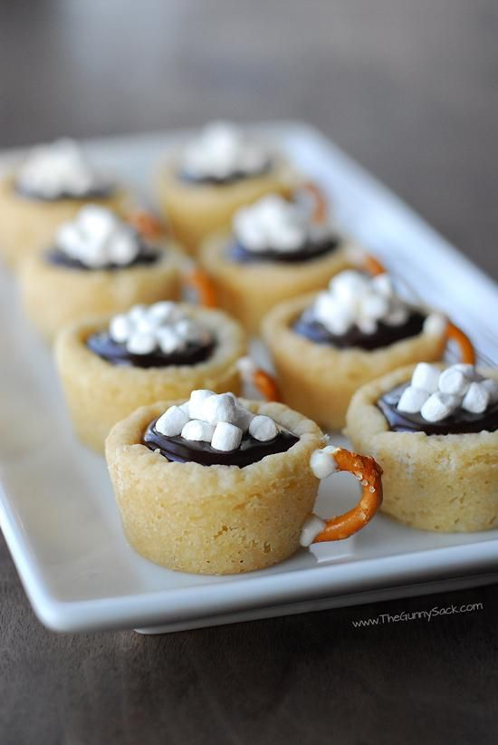 Hot Chocolate Cookie Cups - 1pkg Sugar Cookie Dough 1/2c heavy cream 2TBS hot cocoa mix 1c chocolate chips 1/2c white choc chips 12 mini pretzels 1 c Mallow Bits 1.Put1 TBS dough in mini muffin tin. Bake 12-14 min @ 350. Cool before gently removing Bring chocolate to boil. Stir in cocoa mix.  Pour hot cream over the choc chips let it sit 3 min.stir  Melt white chips and use it to attach the pretzel handles to the cookie cups.  Spoon the chocolate ganache into cups and top with mini marshmallows