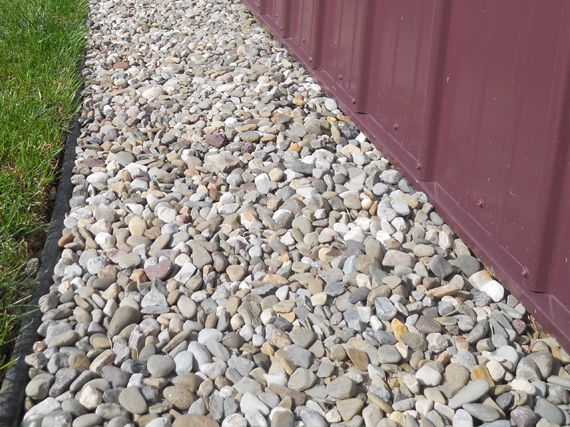 Rock landscape edge around structure in the garden for Smooth stones for landscaping