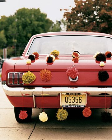 A shiny 1965 Mustang, strung with handmade pompoms