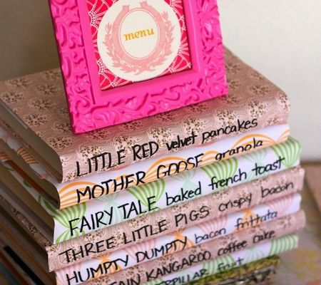 Book Themed Baby Shower - Book Party Menu: A clever way to display your book party menu is on a stack of books. (This baby shower centered around classic fairytales, which is yet another direction to go with this theme.) See more of this vintage storybook shower from Kojo Designs